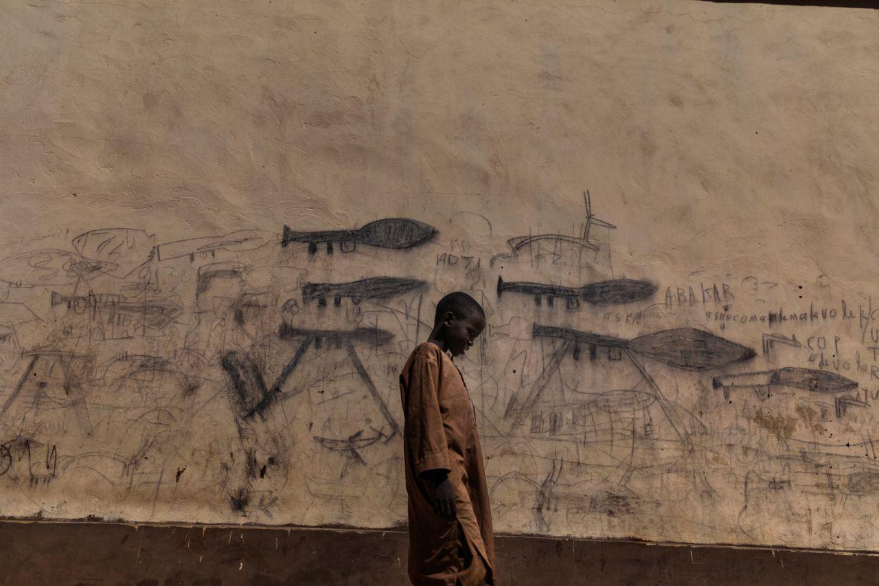 Un niño huérfano pasa junto a una pared con dibujos que muestran lanzadores de granadas propulsados ??por cohetes en Bol, Chad.