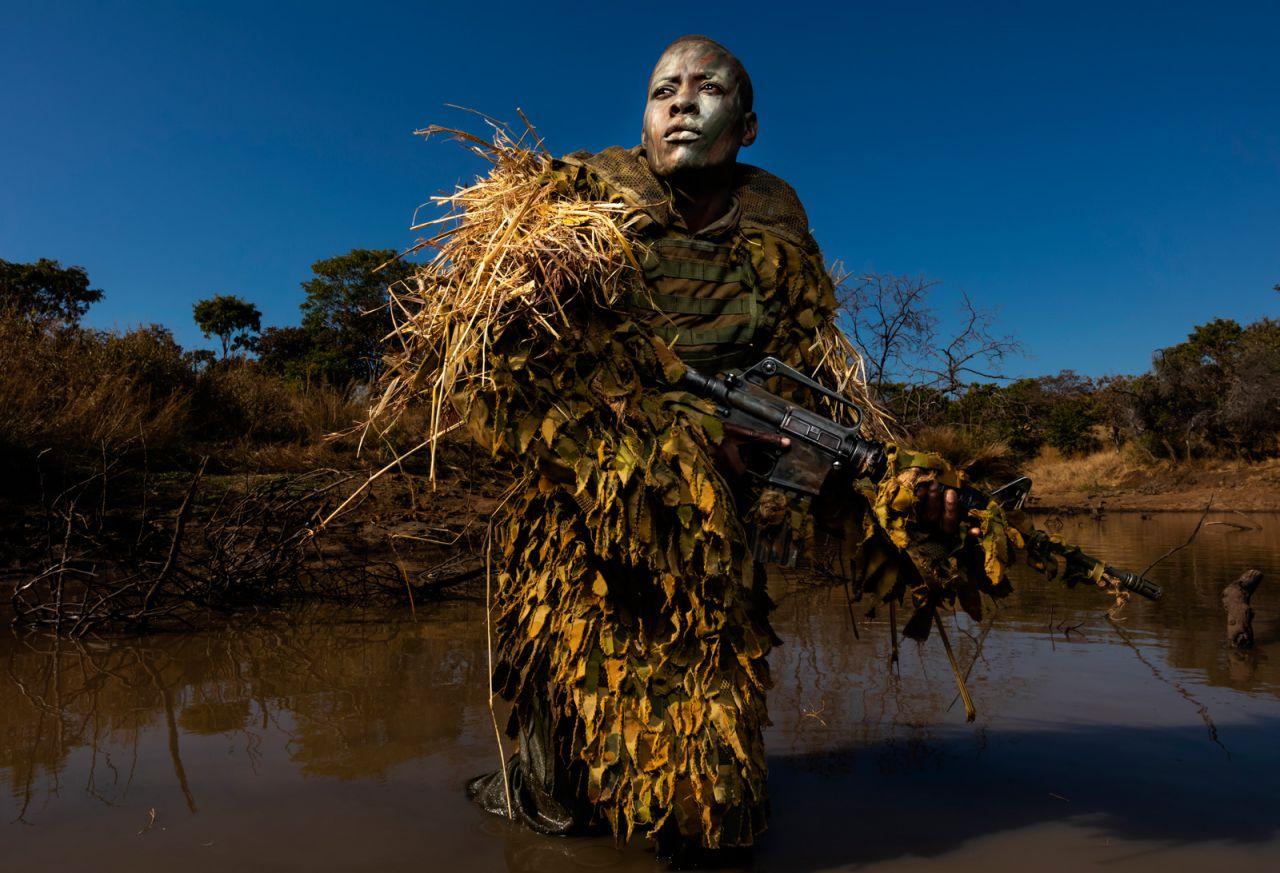 Petronella Chigumbura (30), miembro de una unidad femenina contra la caza furtiva llamada Akashinga, participa en entrenamiento de ocultación y ocultamiento en el Parque de Vida Silvestre de Phundundu, Zimbabwe.
