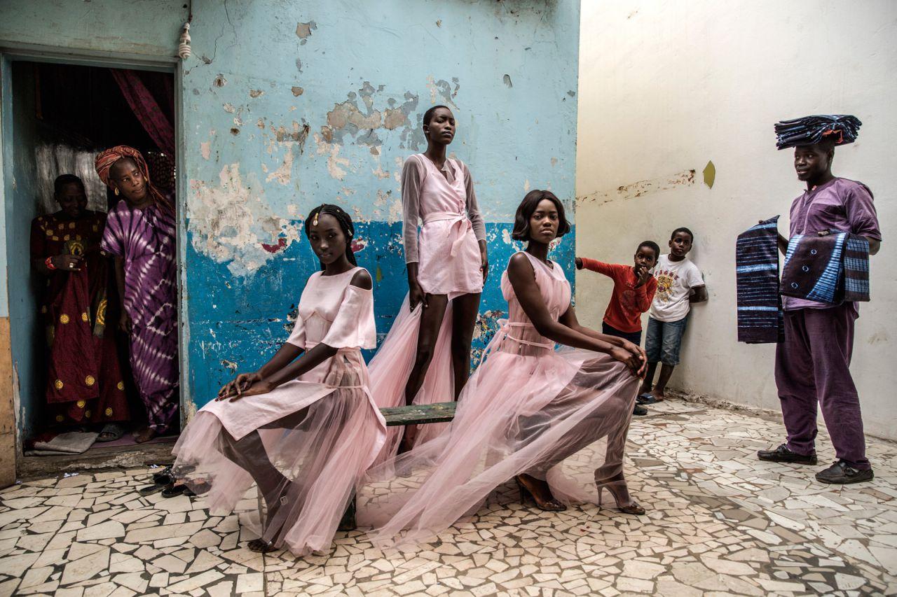 Diarra Ndiaye, Ndeye Fatou Mbaye y Mariz Sakho visten atuendos del diseñador Adama Paris, en el barrio de Medina en la capital senegalesa, Dakar, mientras los curiosos residentes miran.