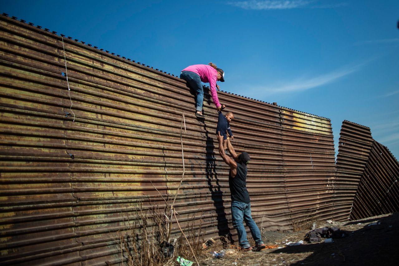 Los migrantes centroamericanos trepan la frontera entre México y los Estados Unidos, cerca del cruce fronterizo de El Chaparral, Tijuana, Baja California, México, el 25 de noviembre de 2018.