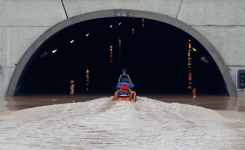 Varios miembros de los servicios de rescate cruzan en moto acuática la salida del túnel de la AP-7 a la altura del municipio alicantino Pilar de la Horadada.