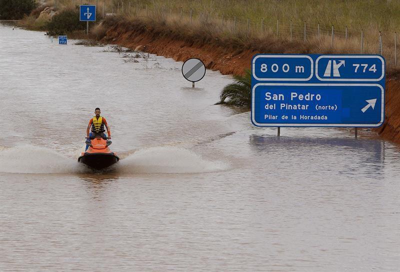 Un miembro de los servicios de rescate cruza en moto acuática la salida del túnel de la AP-7 a la altura del municipio alicantino Pilar de la Horadada.