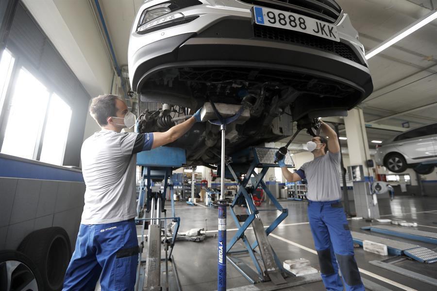Dos mecánicos protegidos con mascarillas intervienen en un coche en un taller en Bilbao