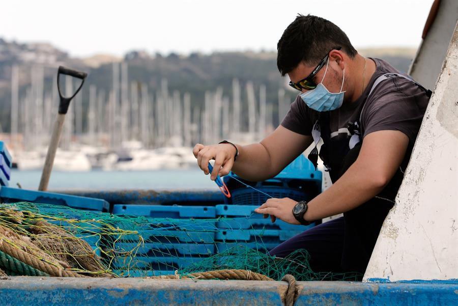 Un marinero repara una red en el puerto de Denia (Alicante) tras salir a faenar tras el parón decretado por el estado de alarma.
