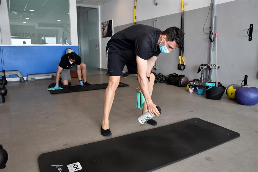 Dos entrenadores del centro deportivo SUMA en Almería desinfectan las instalaciones tras un entrenamiento personalizado con un cliente.
