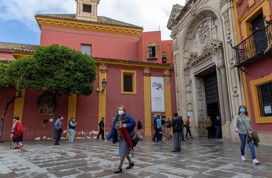 Varios fieles con mascarillas y guardando la distancia entran y salen del interior de la Basílica de Jesús del Gran Poder tras la misa celebrada hoy.