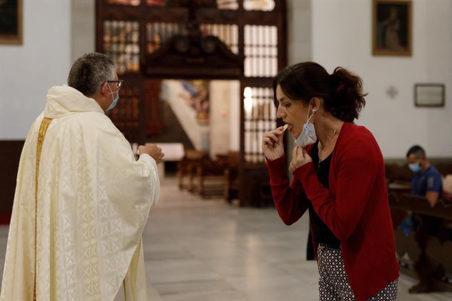 Una mujer toma la comunión durante la eucaristía celebrada en la Basílica de Candelaria, Tenerife.