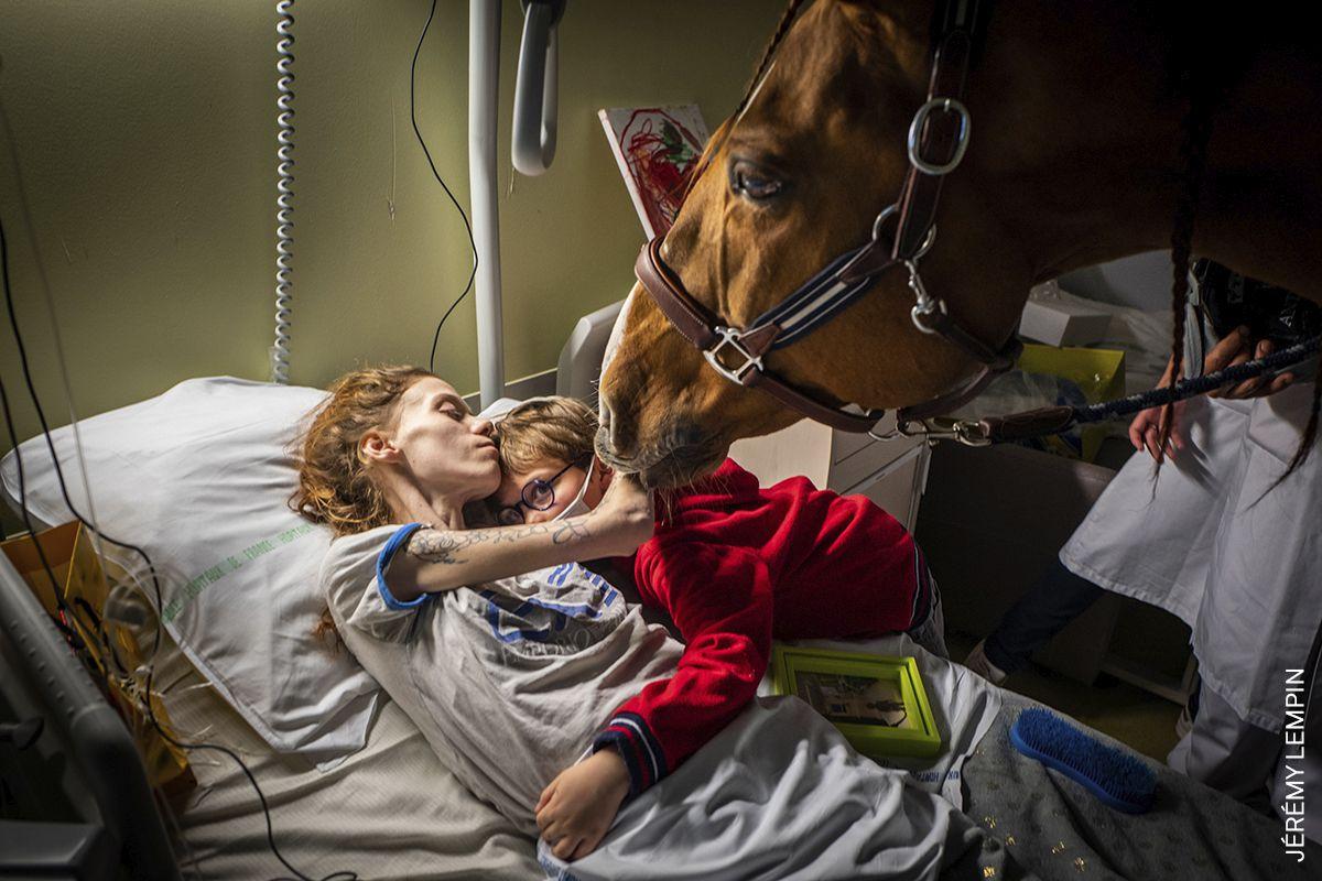 Marion (24), que tiene cáncer metastásico, abraza a su hijo Ethan (7) en presencia de Peyo, un caballo utilizado en terapia asistida por animales, en la Unidad de Cuidados Paliativos Séléne del Centro Hospitalario de Calais, en Calais, Francia.