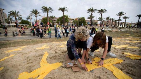 Protesta independentista con cruces en la playa de Mataró.