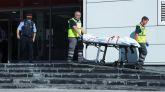Miembros del servicio judicial retiran el cadáver del hombre que ha sido abatido esta mañana al intentar acceder a la comisaría.