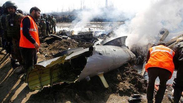 Miembros de la Fuerza Estatal de Respuesta ante Desastres inspeccionan los restos de un avión de combate que se estrelló este miércoles a unos 20 km de Srinagar, capital estival de la Cachemira india.
