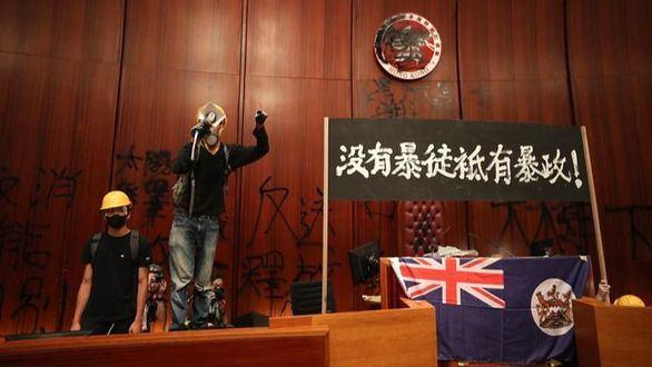 Un protestante ofrece un discurso, con la bandera colonial de fondo, en el Parlamento de Hong Kong.