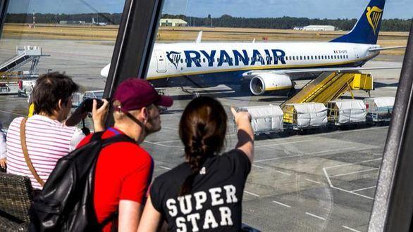 Varios pasajeros observan un avión de la aerolínea Ryanair en el aeropuerto de Eindhoven (Holanda).