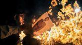 Varios manifestantes queman fotos del rey Felipe este lunes, durante una concentración convocada por los CDR en Gerona.