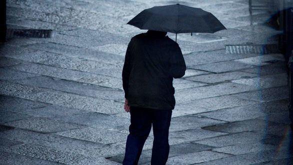 Una persona se protege de la lluvia este viernes en el casco viejo de Ourense.
