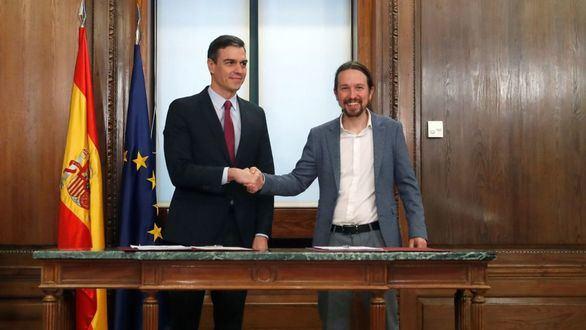 El candidato a la investidura, Pedro Sánchez (i), y el líder de Podemos, Pablo Iglesias (d), estrechan sus manos durante el acto de firma del acuerdo programático con las principales medidas que tomará el futuro Gobierno de coalición.