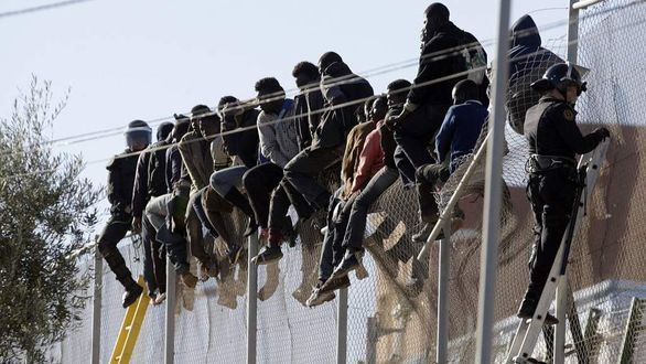 Varios subsaharianos en el vallado entre Melilla y Marruecos.