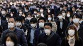 Trabajadores protegidos con mascarillas acuden a sus oficinas en Tokio, Japón, este lunes