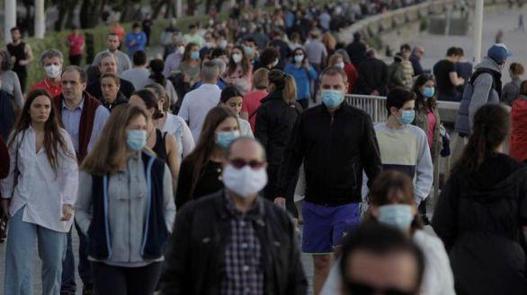 Docenas de personas pasean este sábado por la playa del Orzán de La Coruña.