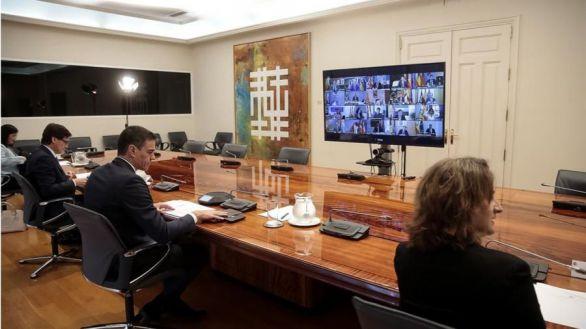 El presidente del Gobierno, Pedro Sánchez (2-d), acompañado por sus ministros de Sanidad, Salvador Illa (2-i), y Transición Ecológica, Teresa Ribera (i), mantiene una videoconferencia con los presidentes autonómicos en el Palacio de la Moncloa, este domingo en Madrid.