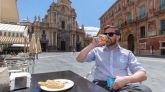 Un hombre toma una cerveza y una marinera, tapa típica de Murcia, en una terraza de la Plaza de Belluga.