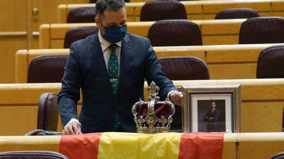 Un senador del PP recibe a Iglesias con una corona y un retrato del Rey