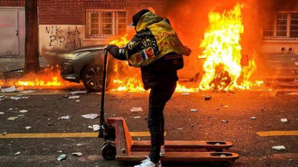 Un manifestante mueve una carretilla mientras un coche arde, en París.