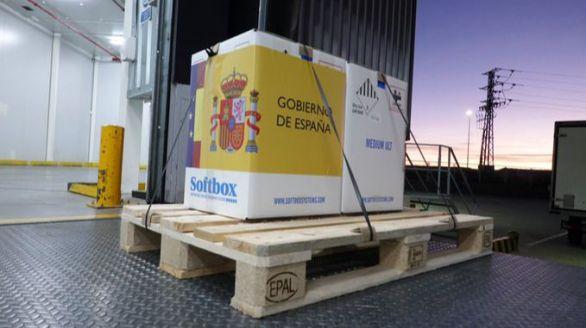 Caja con las primeras dosis de la vacuna de Pfizer llegadas a España, recubierta con el logo del Gobierno.