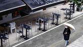 Un viandante camina cerca de una terraza en Oviedo, donde los bares y restaurantes han permanecido 40 días cerrados.