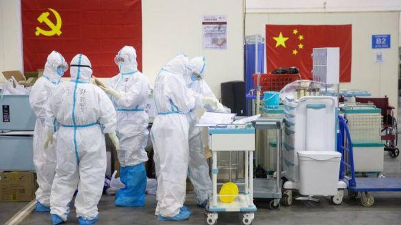 Personal médico con trajes protectores trabajando en el hospital provisional de Wuhan.
