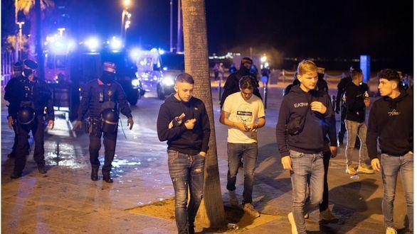 Varios jóvenes abandonan la playa de la Barceloneta mientras la policía los desaloja.