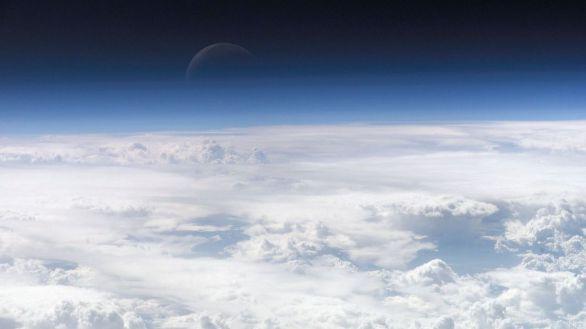 Vista de la atmósfera terrestre con la luna al fondo.