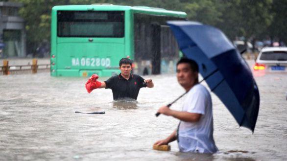 Habitantes de Zhengzhou tratan de hacerse paso por las calles de la ciudad.