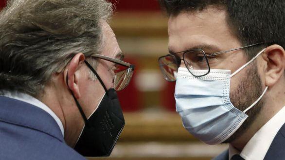 El presidente catalán, Pere Aragonés junto al conseller de Economía, Jaume Giró (i), momentos antes de iniciarse hoy el pleno del Parlamento catalán.