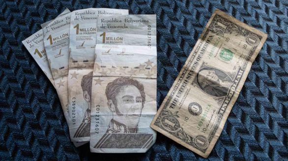 Cuatro billetes de un millón de bolívares junto a su equivalente de un dólar.
