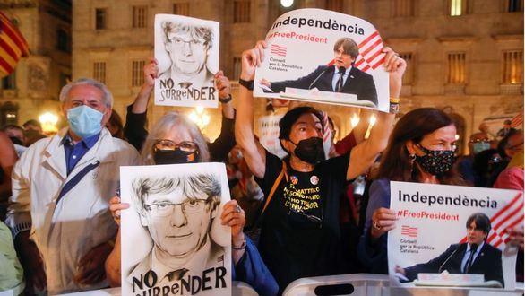 Varias personas sostienen retratos del expresidente de la Generalitat Carles Puigdemont durante las fiestas de la Mercé.