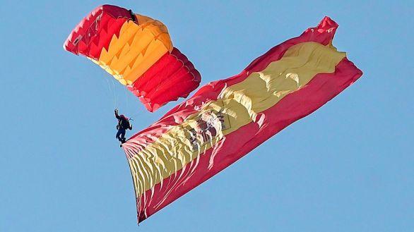 Un paracaidista del Ejército del Aire lleva la bandera de España hasta el desfile de la Fiesta Nacional.