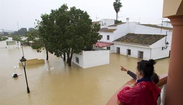 Varias personas observan el estado de sus casas inundadas en la barriada Doña Ana de la localidad de Cártama por las fuertes lluvia caídas esta noche.