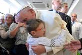 Fotografía cedida por el periódico vaticano L'Osservatore Romano que muestra al Papa mientras saluda a un niño durante su visita sorpresa a la Fundación Santa Lucía