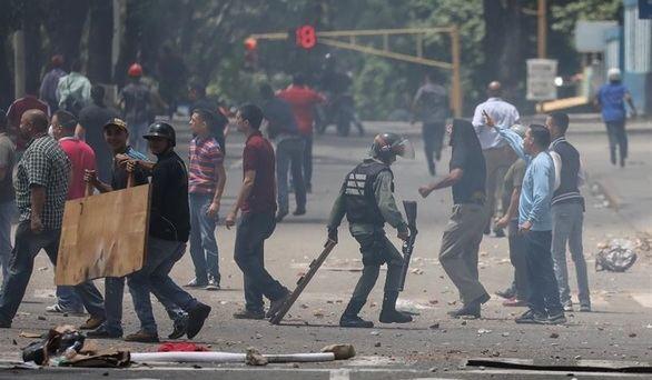Chavistas detienen a un opositor durante unos enfrentamientos con la Guardia Nacional Bolivariana
